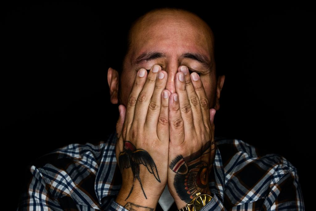 A male PhD student covers his face with his hands in a gesture of stress.