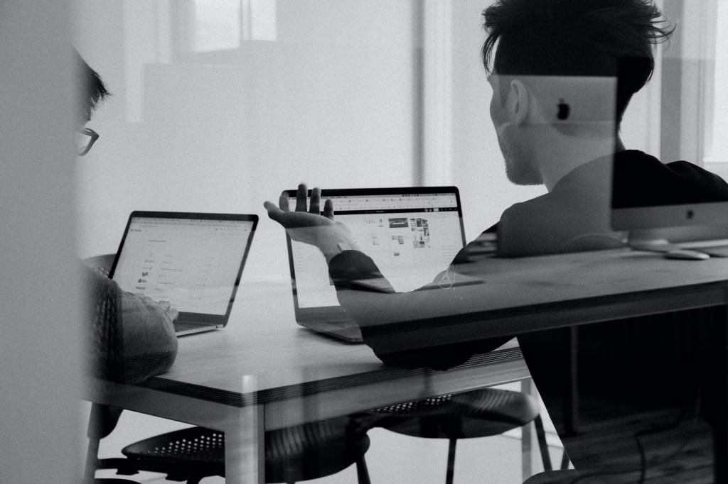 two people sit at a table and work on laptops while holding a discussion.